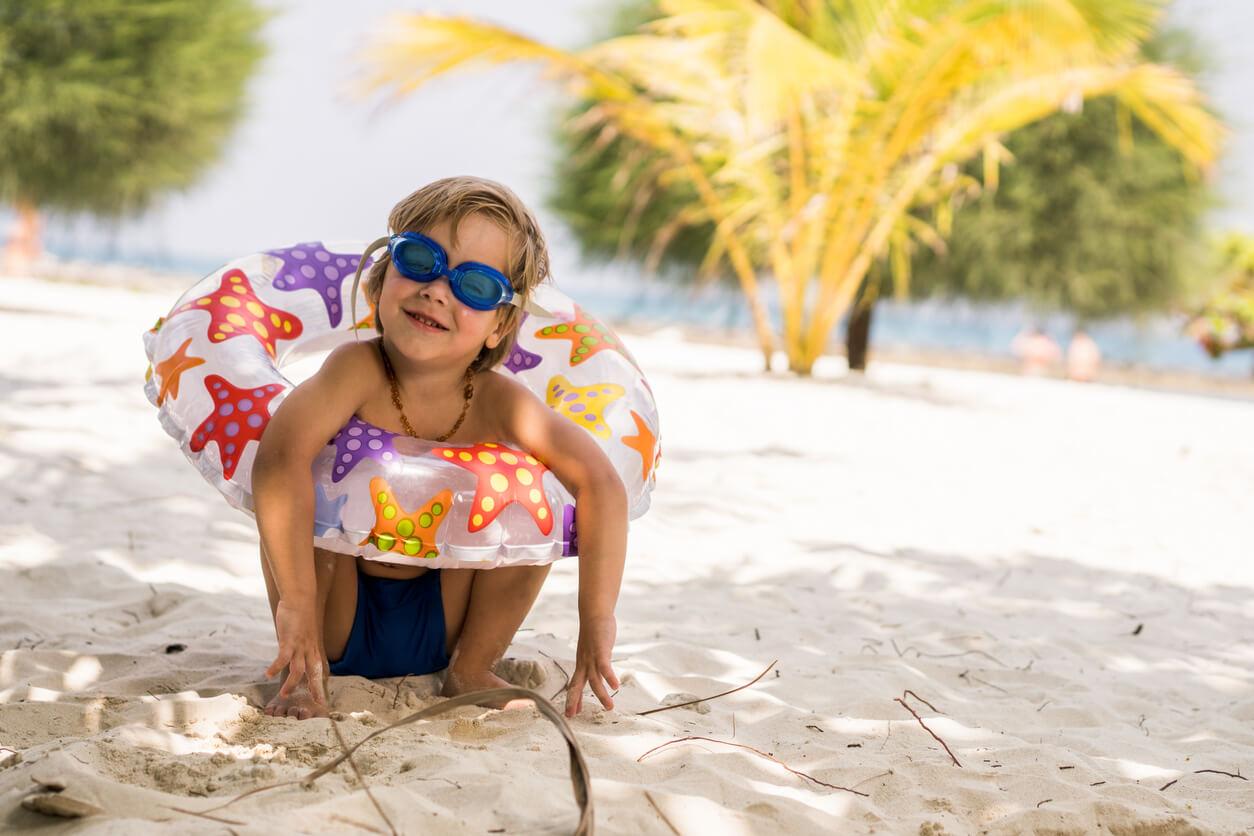Kind sitzt mit Schwimmbrille und Schwimmreifen am Strand.