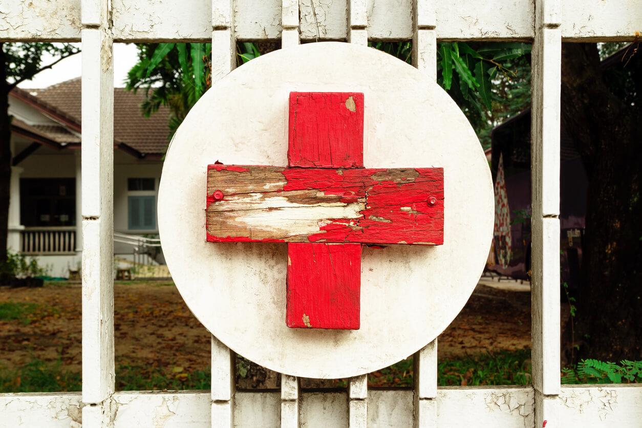 Hölzernes rotes Kreuz auf weißem Grund an einem Tor montiert.