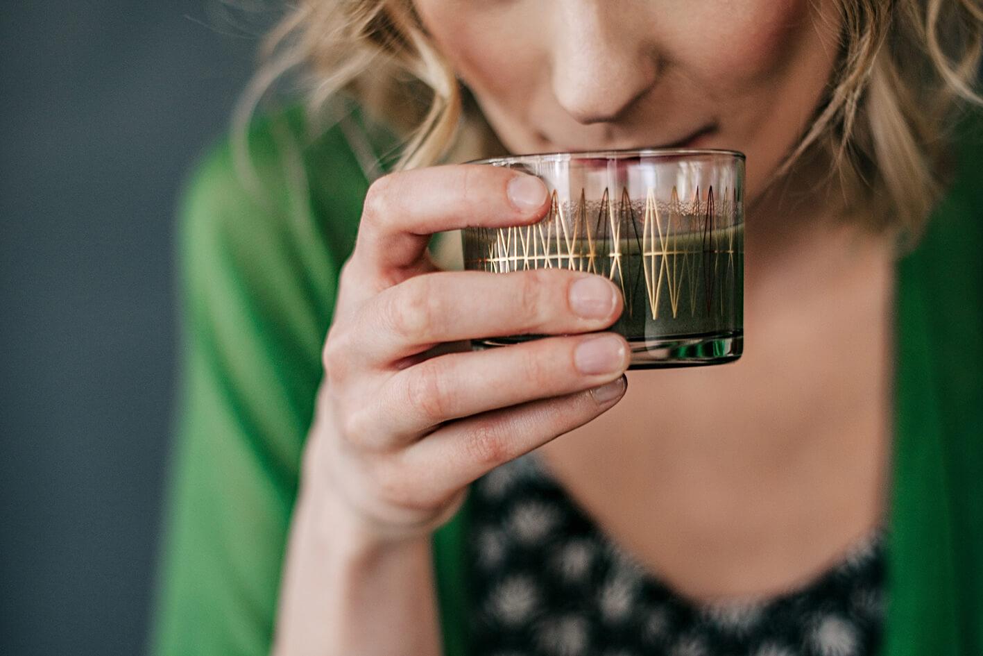 Frau hält Glas mit grünem Getränk.
