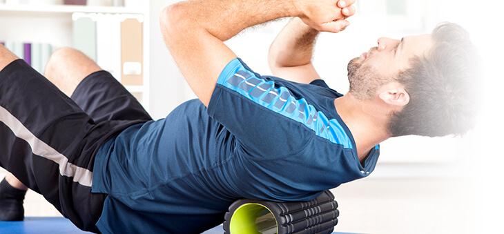 Mann rollt Rücken über Hartschaumrolle.