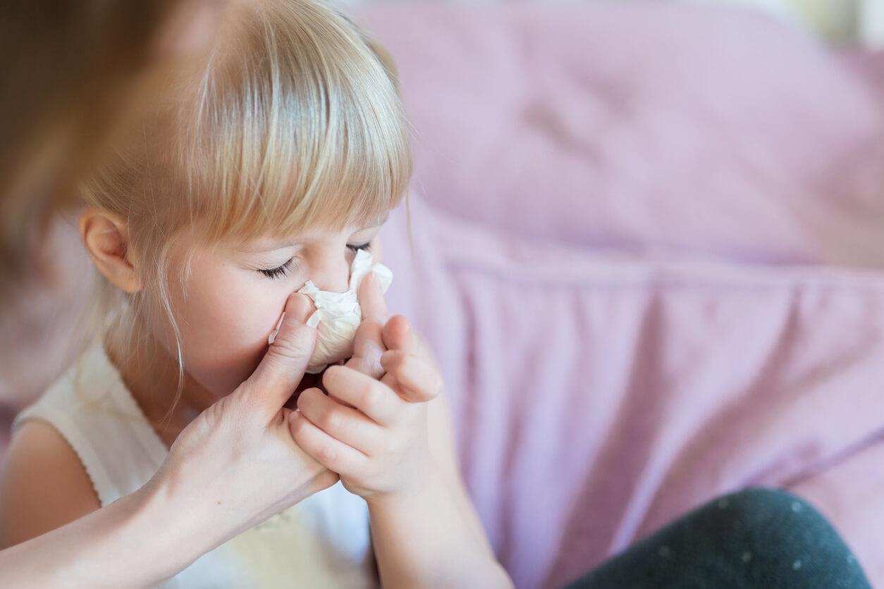 Frau putzt kleinem Mädchen die Nase.