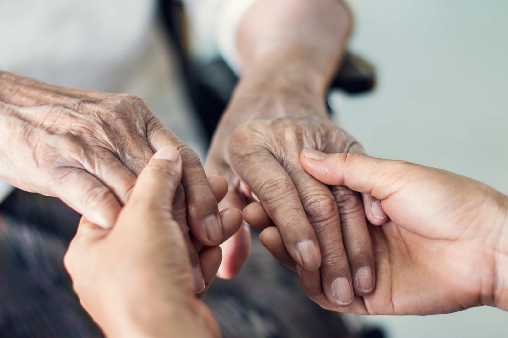 Junge Hände halten ältere Hände.