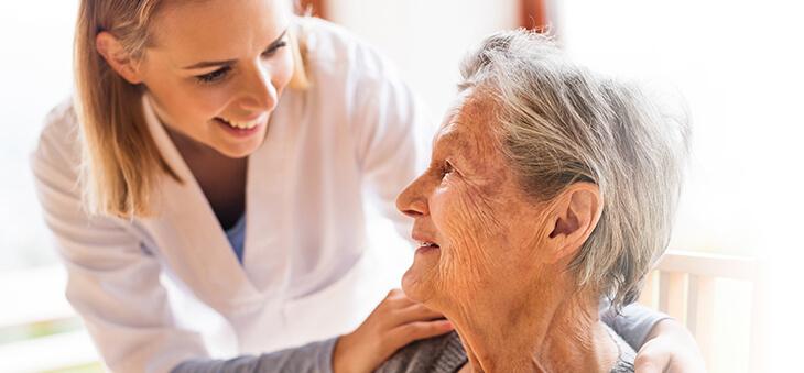 Pflegerin und ältere Dame lächeln einander an.