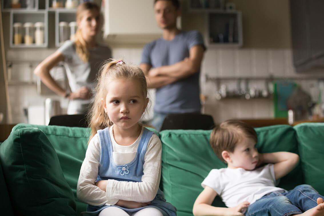 Kleines Mädchen mit verschränkten Armen sitzt neben kleinem Jungen auf dem Sofa; Eltern stehen im Hintergrund.