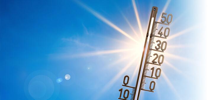 Thermometer vor blauem Himmel und Sonne.