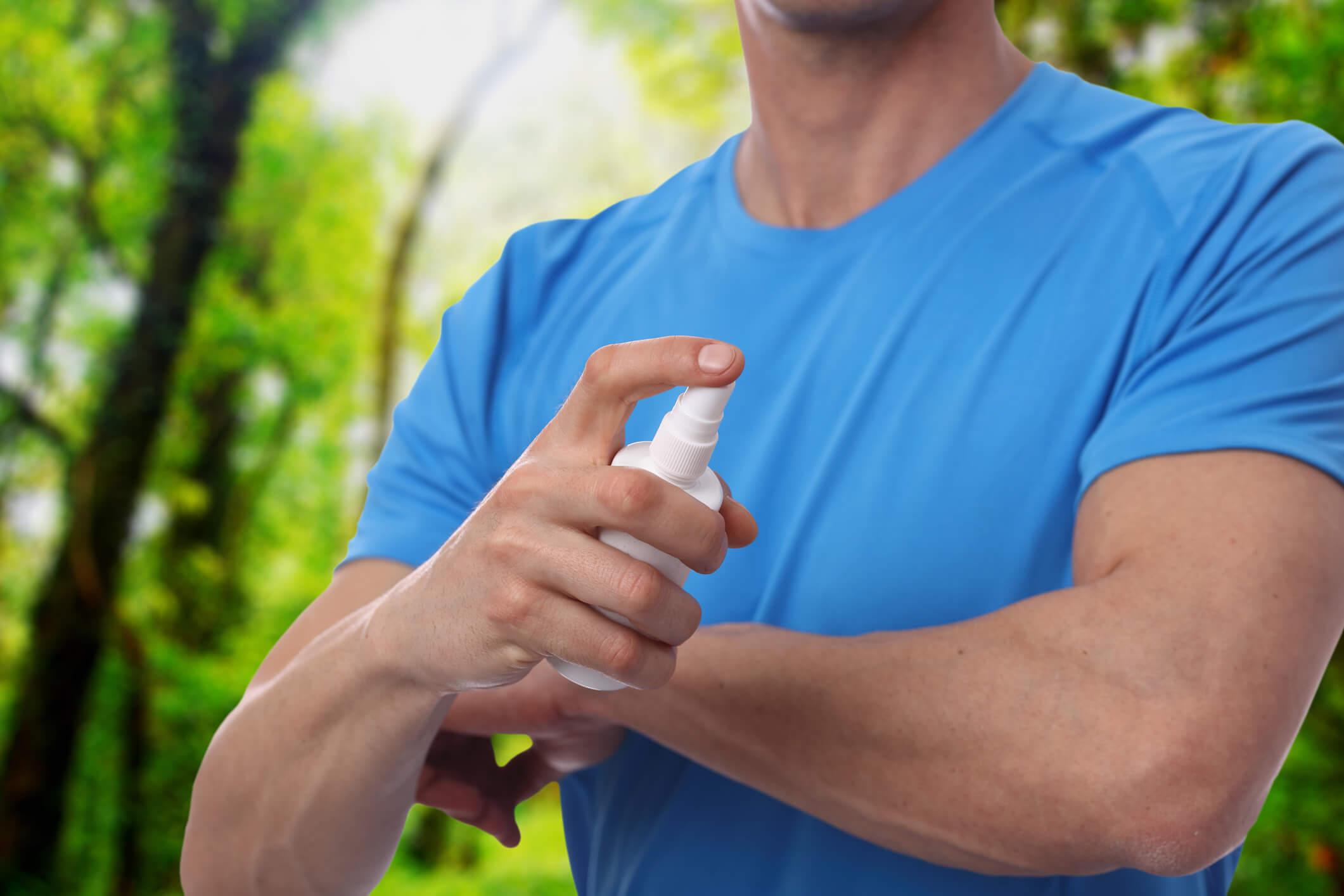 Mann sprüht sich Mückenspray auf den Arm.