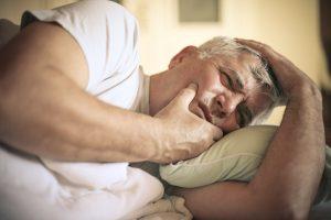 Mann mit Kieferschmerzen und Kieferfunktionsstörungen als Folge von Zaehneknirschen
