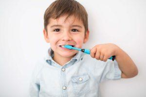 Kind putzt sich die Zaehne mit fluoridhaltiger Zahnpasta
