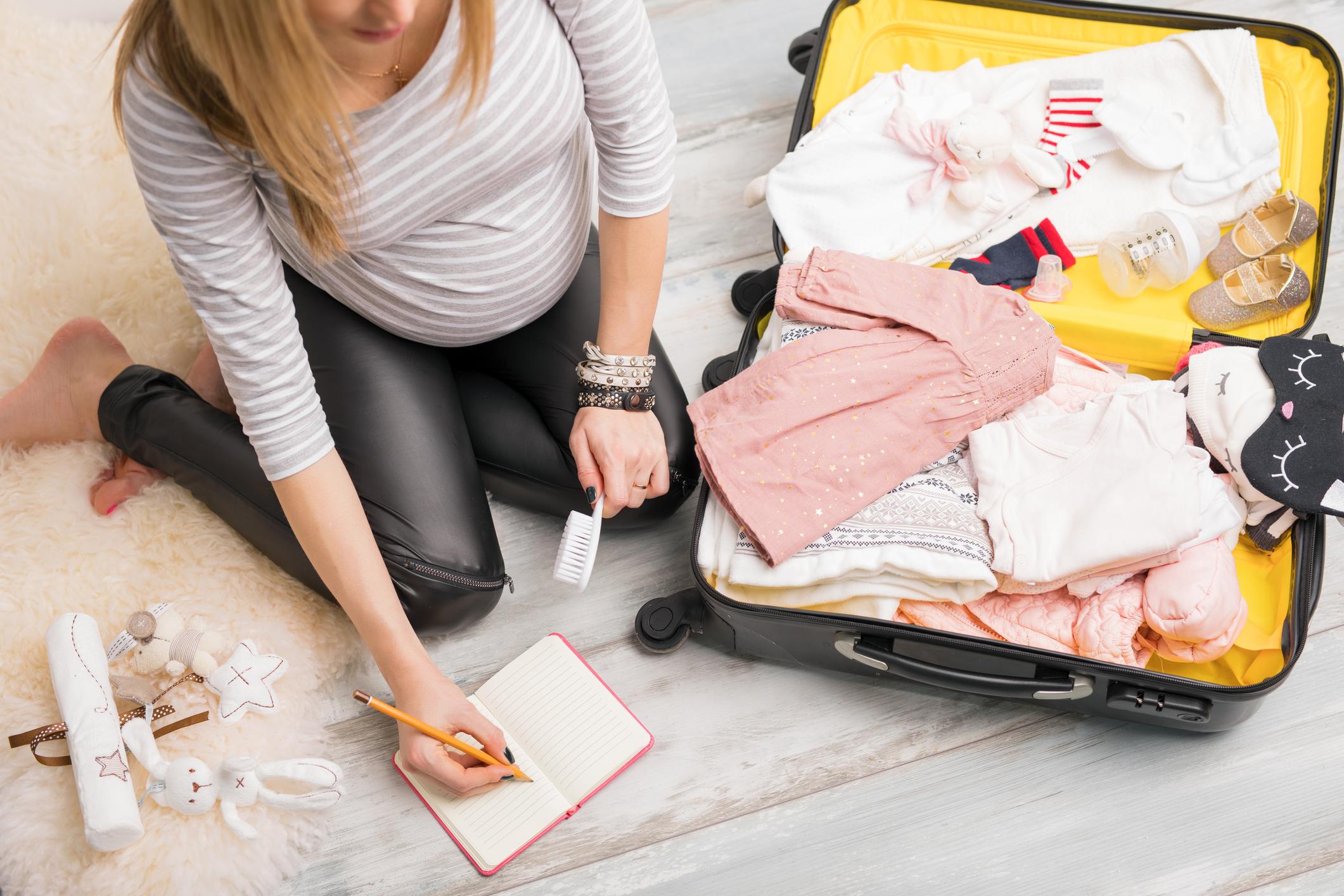 Schwangere Frau packt Babysachen in die Kliniktasche