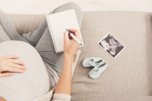 Schwangere Frau macht eine Liste fuer die Kliniktasche.