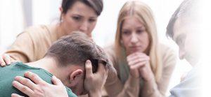 Depression bei Männern – Freunde troesten einen traurigen Mann.