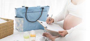 Schwangere Frau packt ihre Kliniktasche zur Geburt.