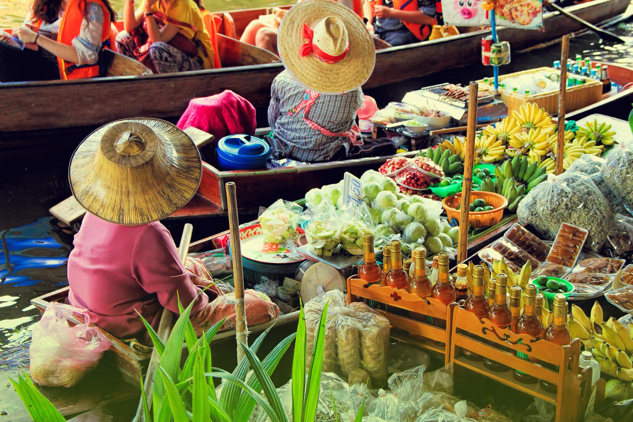Thailaendische Marktfrauen auf Booten – exotische Fruechte im Urlaub richtig geniessen.