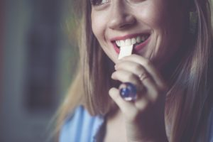 Eine Frau schiebt sich einen Kaugummi in den Mund.