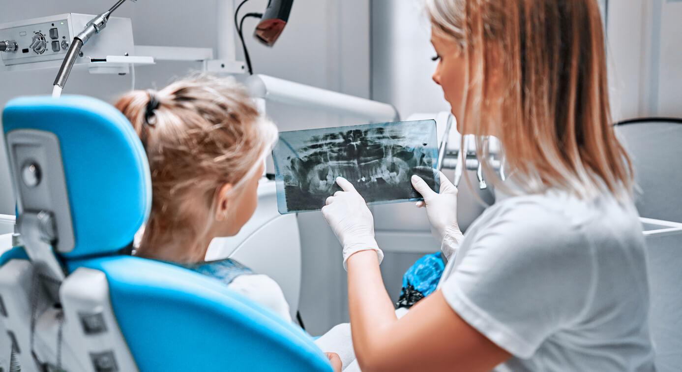 kieferorthopaedin-zeigt-jungem-maedchen-röntgenbild